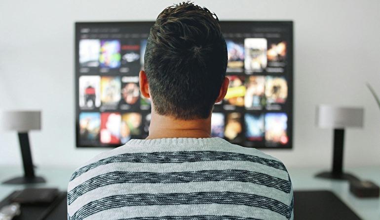 座ってテレビを見ている男性