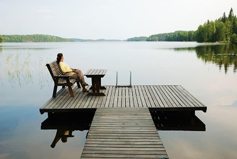 静寂な湖の風景とぼんやり眺める女性