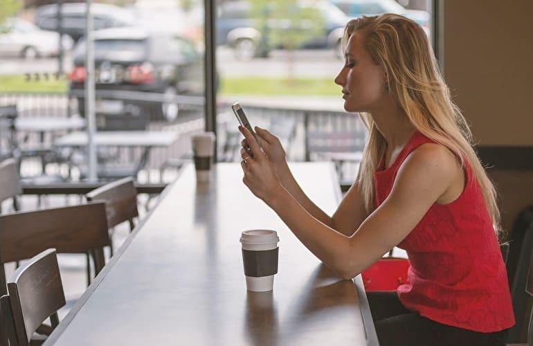 カフェにいて携帯をみている女性とコーヒー