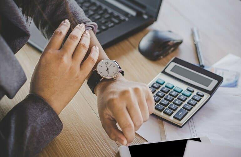 腕時計をみる働く女性