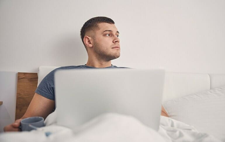 ベッドの中でパソコン男性