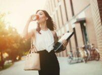 コーヒーを飲みながら歩く女性