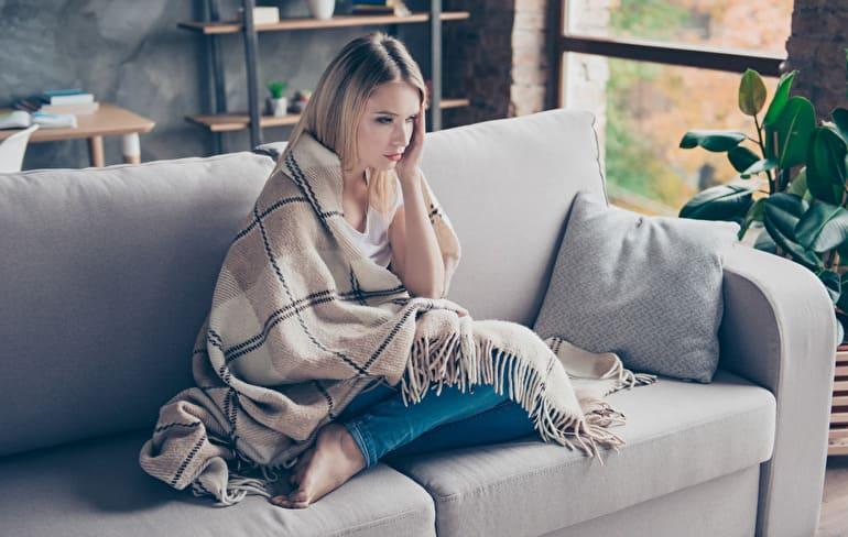 家のソファ不安そうな女性
